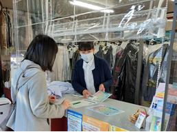 写真:クリーニングされた洋服が並ぶ店内、従業員が、客に洗濯表示早見表マグネットを見せて説明している