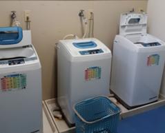 写真:3台の洗濯機が並び、その前面に洗濯表示早見表マグネットが貼られている。